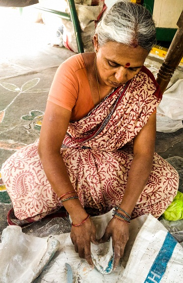 An old woman working on the wooden dancing dolls at Kondapalli Village of Andhra Pradesh