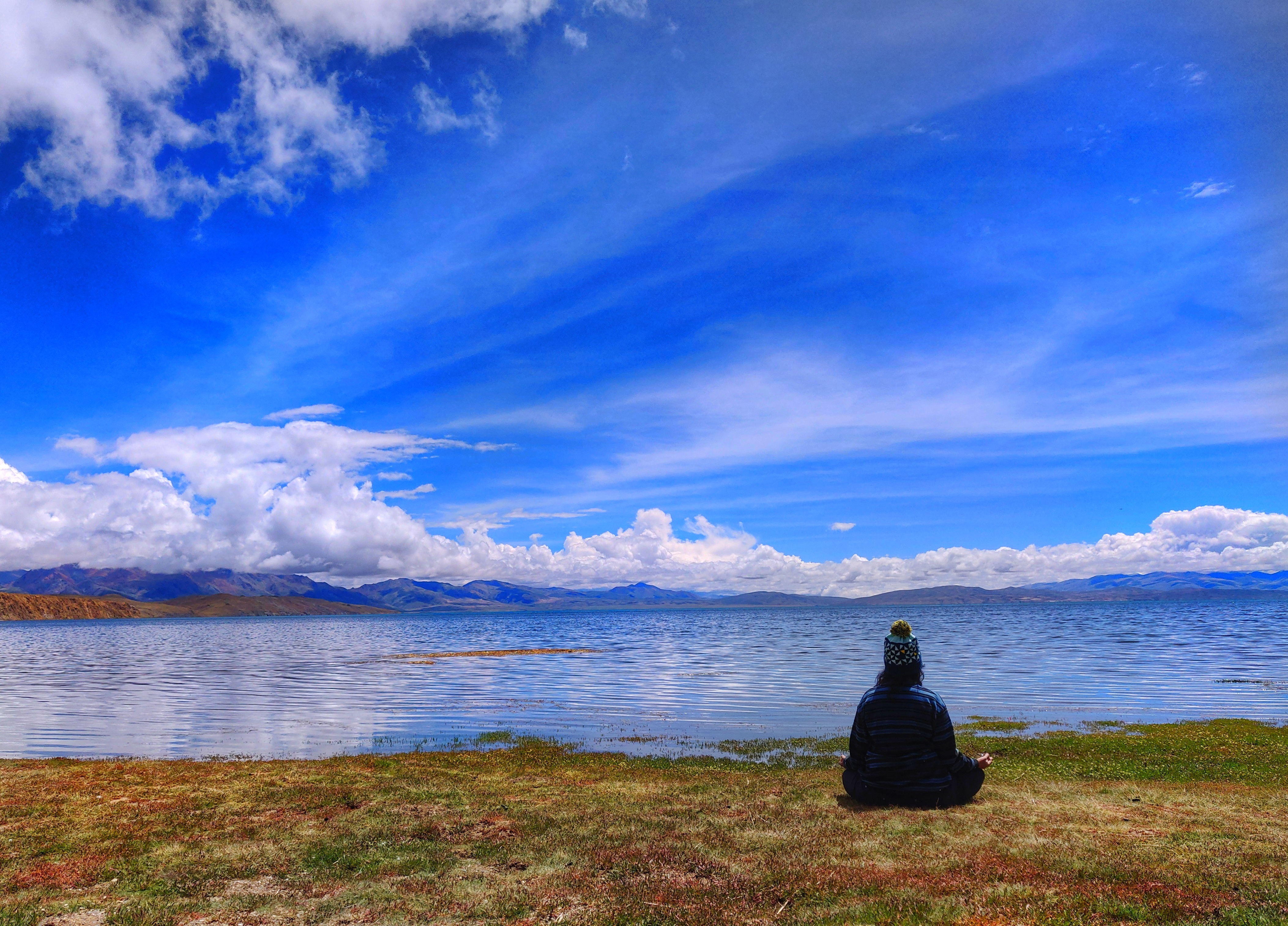 I am sitting by the side of Lake Mansarovar during Kailash Mansarovar Yatra